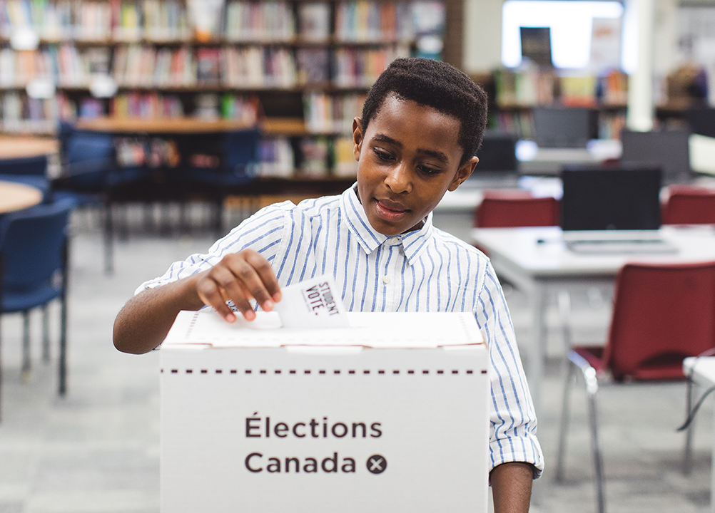 student placing voting card into elections box