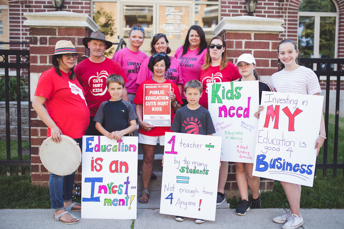 Teachers, parents, students and children holding rally signs