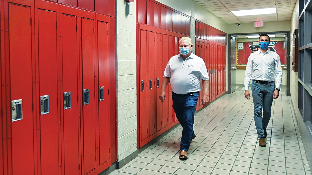 Doug Ford and Stephen Lecce walking down hallway with red lockers