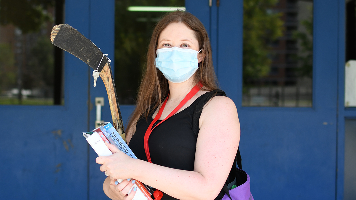 Courtney White standing in front of school wearing mask, carrying books and hockey stick