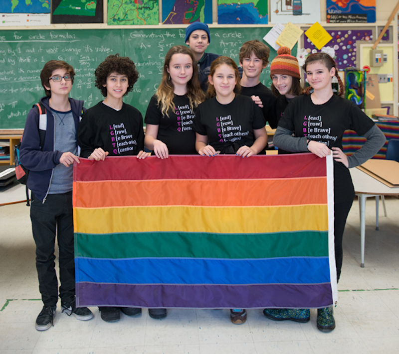 Students standing in classroom holding a rainbow flag