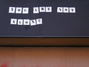 """You are not alone"" typed in letters on sheets on paper taped to blackboard"