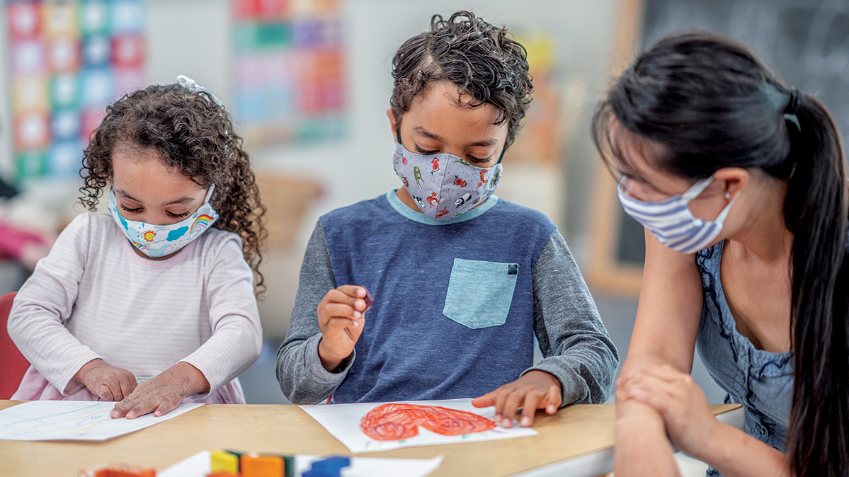 Children and teacher in classroom wearing covid masks