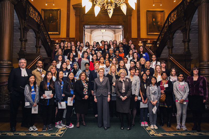 women and girls posing with political leaders