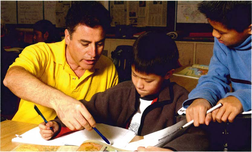 teacher showing elementary student in book