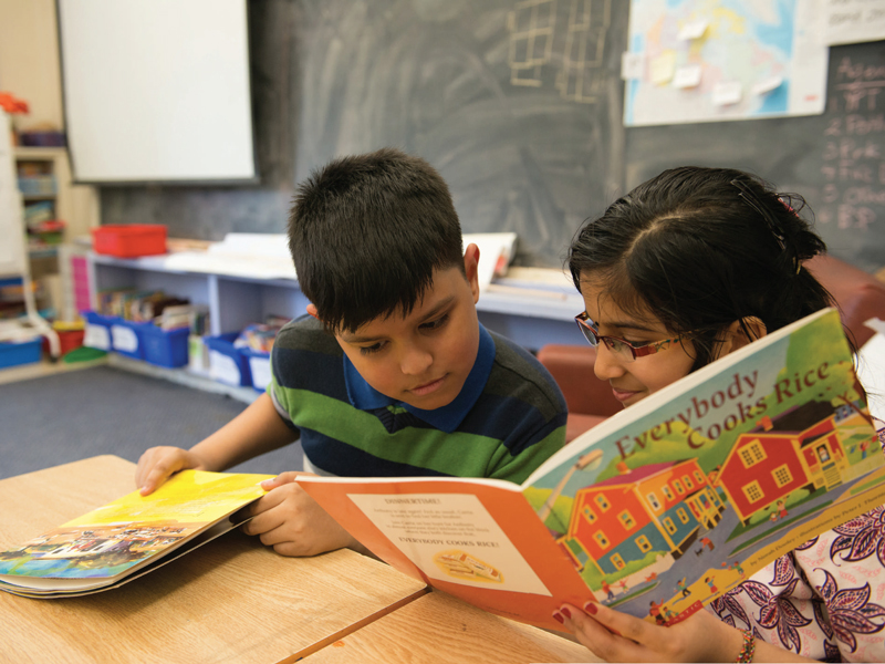 Refugee students reading a book in classroom