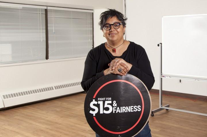 Deena Ladd standing in class holding $15 & Fairness logo