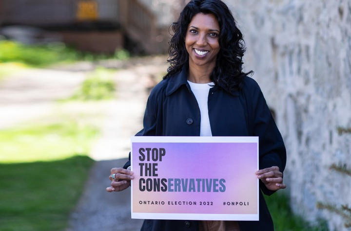 """Cindy Gangaram holding """"Stop the Conservatives"""" sign outside"""