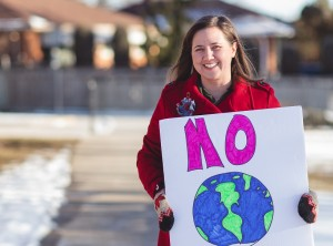 Woman standing outside holding sign