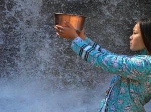 Autumn Peltier holding bowl near waterfall