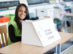 Student volunteer sitting next to vote submission box