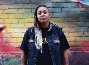 BLM Toronto organizer LeRoi Newbold standing infant of graffiti wall