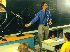 teacher in front of class showing bycilce