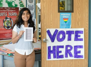 "Student standing beside a sign that reads ""Vote Here"""