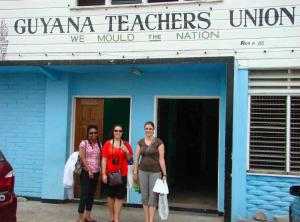 Two female Canadian teachers standing with female President of Guyana Teacher's Union (GTU)
