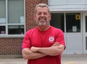 Sam Hammond posing outside of school in red ETFO t-shirt