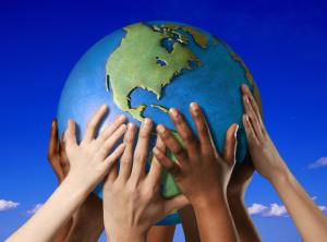Image of Diverse set of hands holding up globe of the world against blue sky background