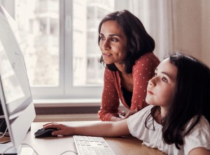 Girl and mother using computer at home