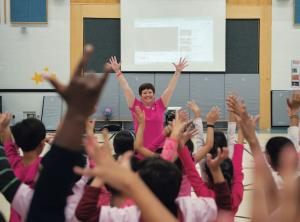 students in gymnasium mimicking teacher who has her hands in the air
