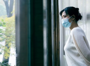 Woman looking out window waring a medical face mask