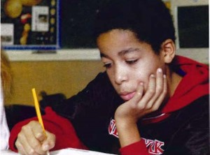 child in classroom looking at workbook