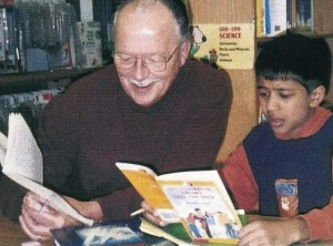 teacher reading with student in library
