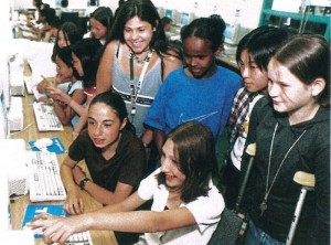 women and children in classroom using computer