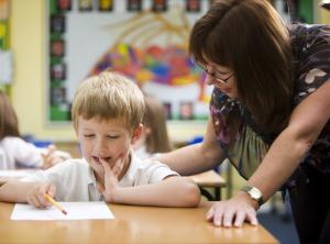 Teacher leaning over elementary student explaining paper in classroom