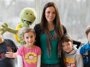 elementary students standing with teacher and puppet