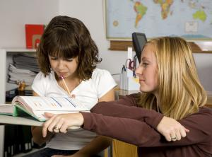 teacher kneeling next to student sitting at desk while they read