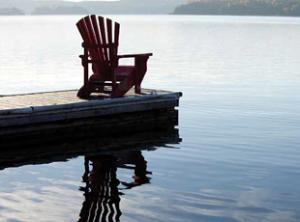 Stock photo of lawn chair on dock over lake with reflection in the water