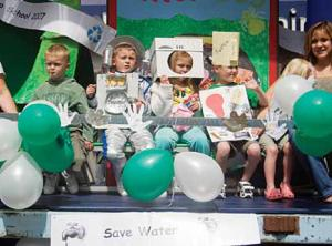 very young students showing recycling projects with green and white balloons in the foreground