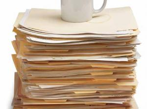 stock image of coffee mug on top of stack of folders