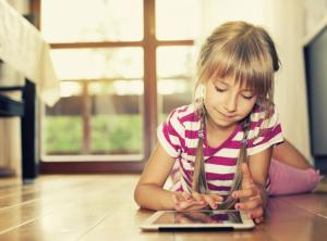 stock photo of young girl laying on floor using a tablet