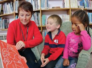 teacher holding a picture book reading to two students in a library