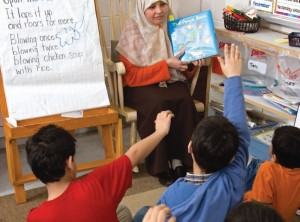 Teacher reading book to students with their hands up