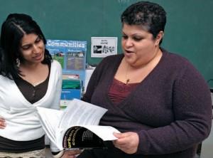 Two teachers flipping through textbook