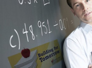 Teacher posing next to blackboard with mathematical equations written on it