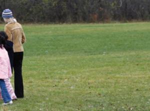 Teacher and students walking across grassy field