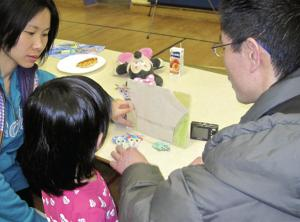 Parents with child looking at the child's work