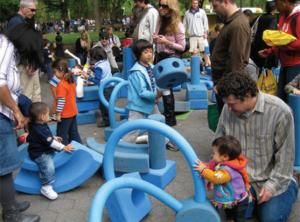 very young children playing in playground with adults