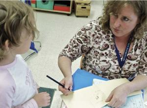 teacher working with kindergarten student