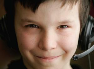 young boy with computer headset smiling looking at camera
