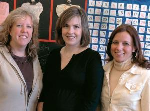 Three woman teachers posing in classroom