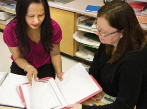 two teachers reading a report