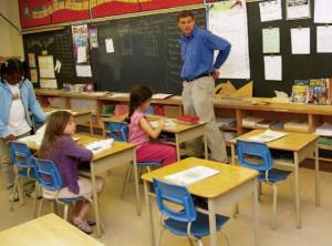 teacher standing in front of classroom while children are working