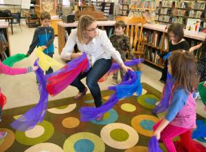 Teacher dancing with elementary students holding colourful feathers