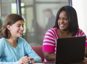 Teacher and student, smiling, looking at laptop