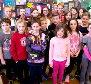 Children standing with teacher in classroom