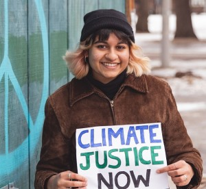 "Savi Gellatly-Ladd holding ""Climate Justice Now"" sign"